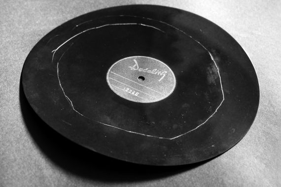 Stephan Mathieu - Radiance Interview, bent black record with white circular scratch mark