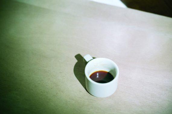 Marc Baron - Un salon au fond d'un lac, a white cup of coffee sat on a wooden table