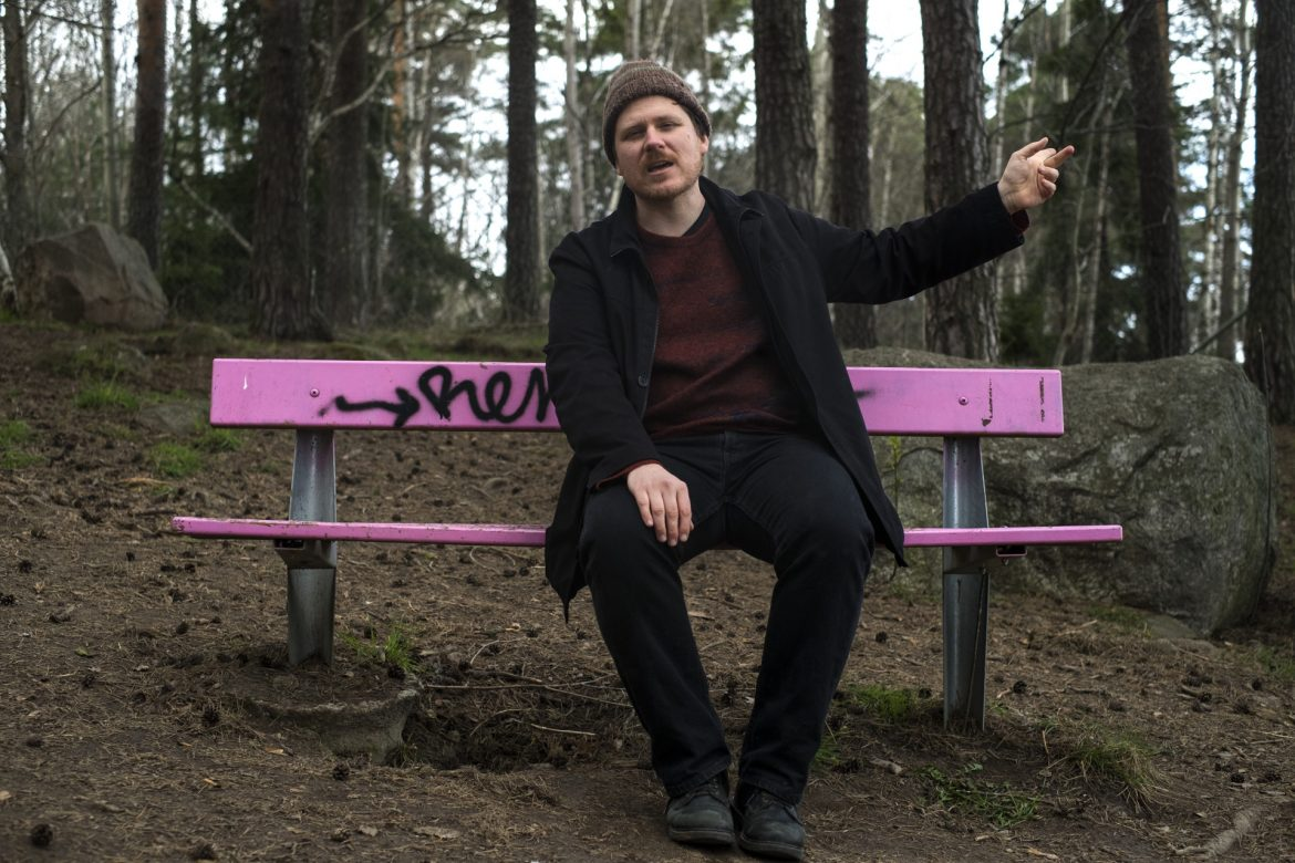 John Chantler sat on a pink park bench surrounded by forest, pointing behind him