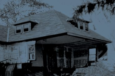 Olivia Block - Dissolution, blue-tinted photograph of a ruined house with some external walls missing, giving a view of a wallpapered room