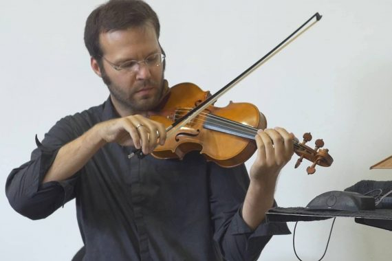 Erik Carlson, artist in blue shirt playing a violin