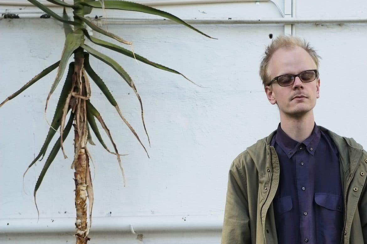 Johan Lindvall - solo/ensemble, composer with his eyes closed stood next to a tall tropical plant