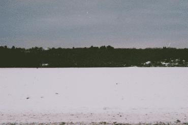 Clara de Asís + Bruno Duplant - L'inertie, dark shore seen from the middle of a frozen snow-covered lake, cobalt sky