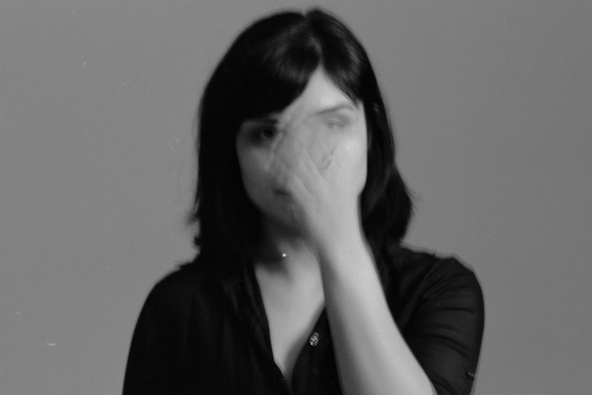 Sarah Davachi - All My Circles Run, black and white photo of artist waving her hand in front of her face