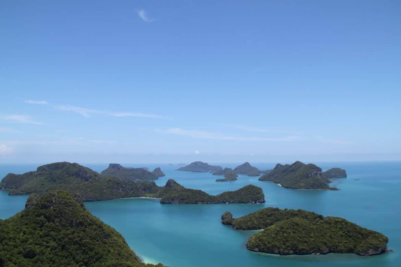 Archipelago by Dmitry Teslya, archipelago of small green islands in a blue sea beneath a blue sky