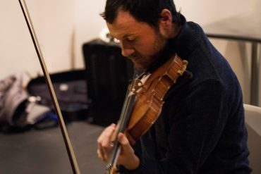 Morgan Evans-Weiler - Unfinished Variations, the artist in a dark jumper holding a violin.