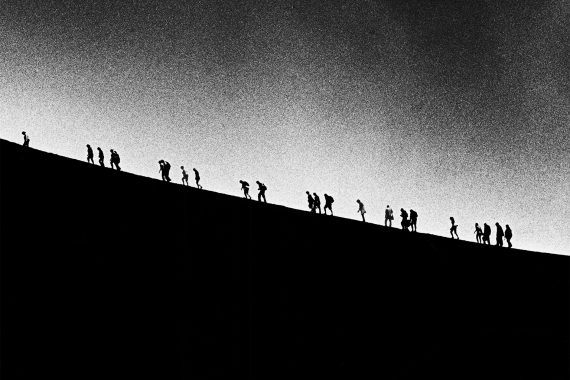 Scott Worthington - Orbit, silhoettes of people climbing a hill against a big grey sky.