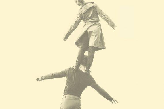 Machinefabriek - Engel, female dancer stood on male dancer's shoulders against a pale yellow background