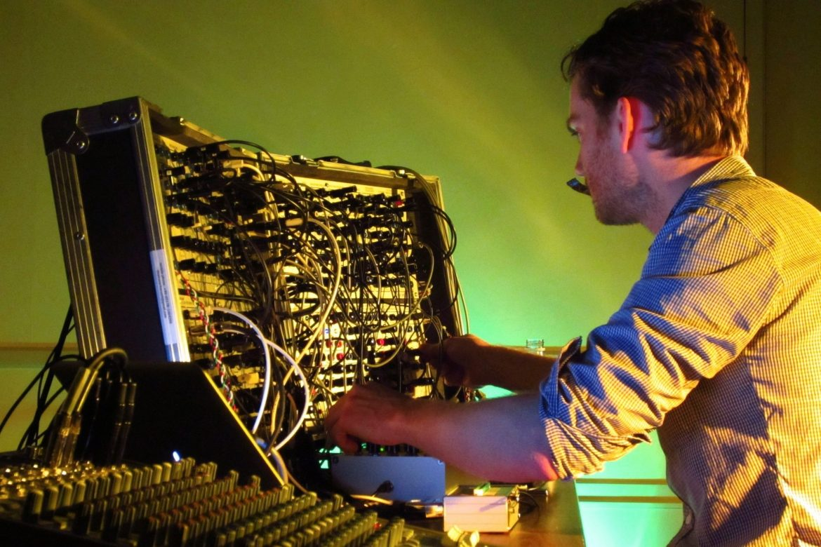 Thomas Ankersmit - Homage to Dick Raaijmakers, artist performing with Serge Modular Synth against a yellow background.