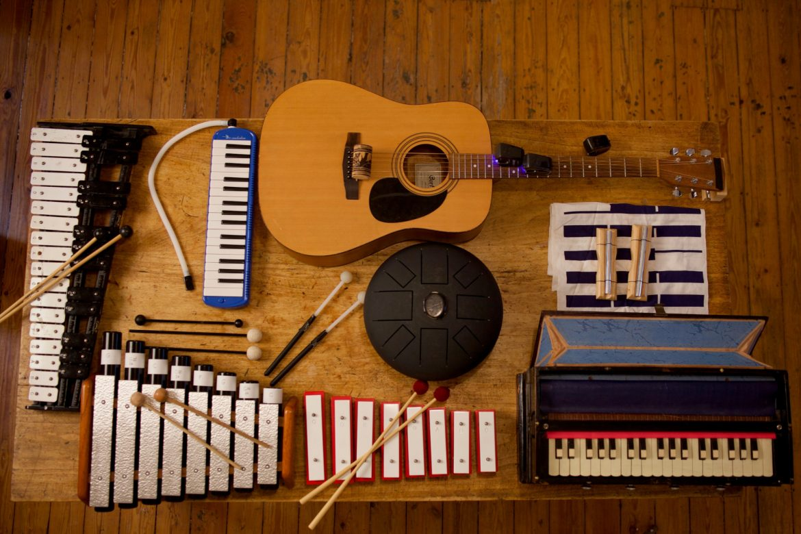 Ensemble 0 - plays eight compositions, top-down view of a guitar, glockenspiels, harmonium, metallophone, and other instruments laid on a table.